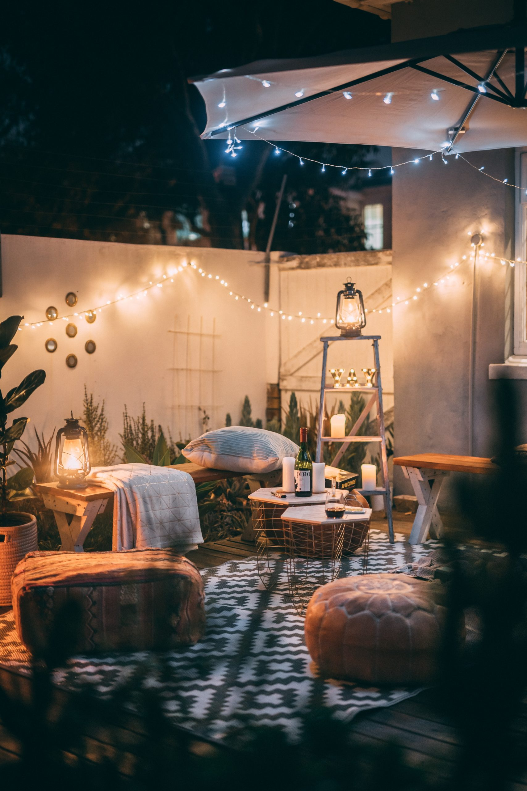 a backyard with outdoor furniture, a white privacy fence and fairy lights